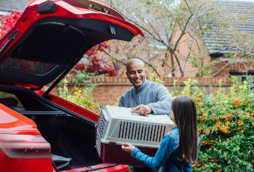 A young girl helps her father unload a pet crate from the trunk of their car.